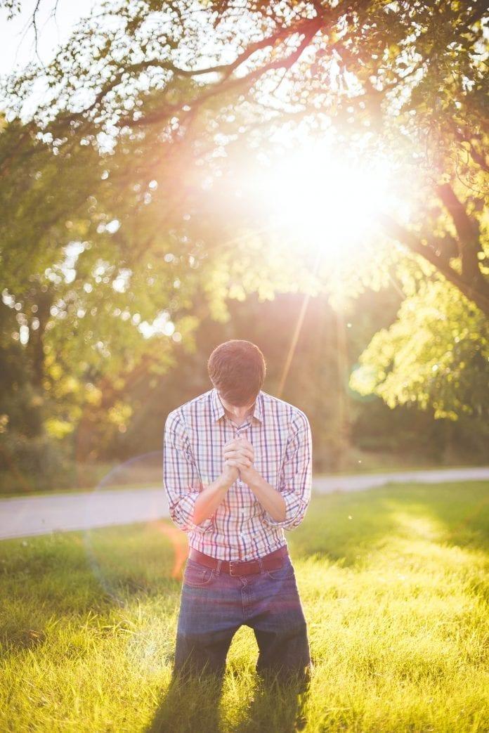 jaunas vyras meldžiasi saulėje