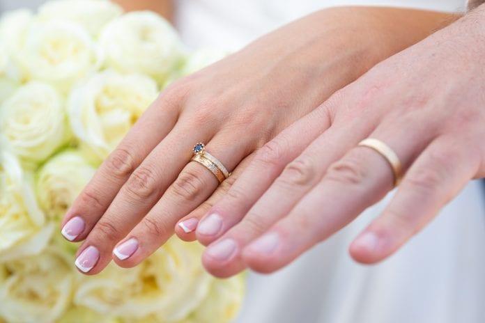 Vestuvių žiedai ant sutuoktinių rankų