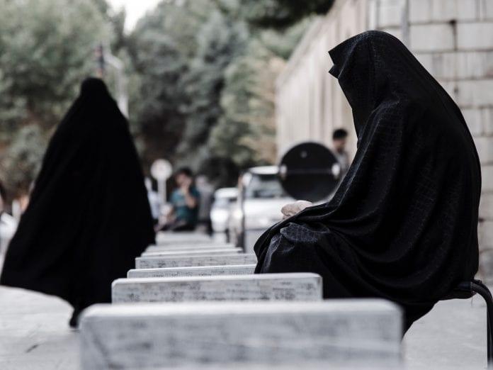 Moteris su burka sėdi