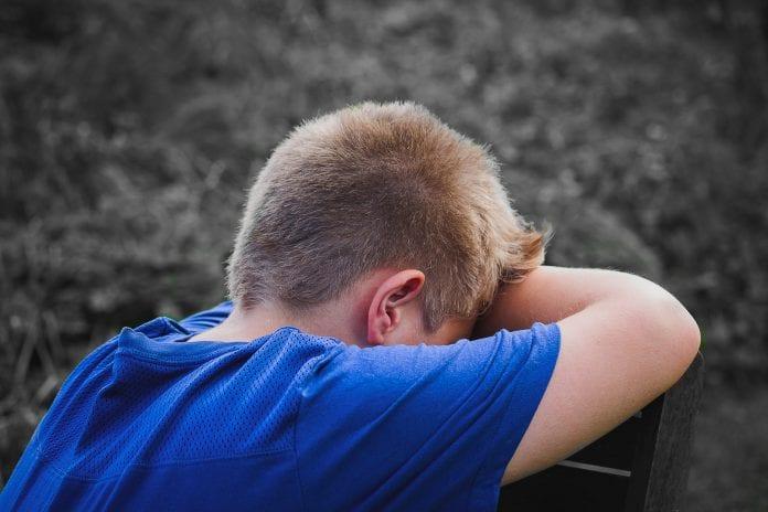 Berniukas verkia padėjęs galvą ant sulenktų rankų