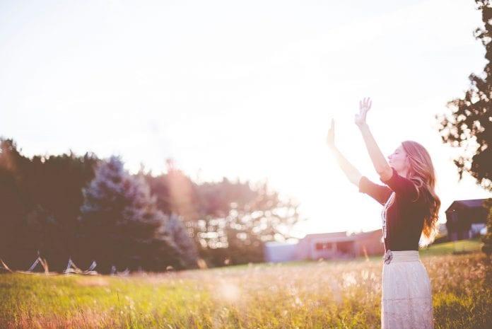 moteris kelia rankas į dangų