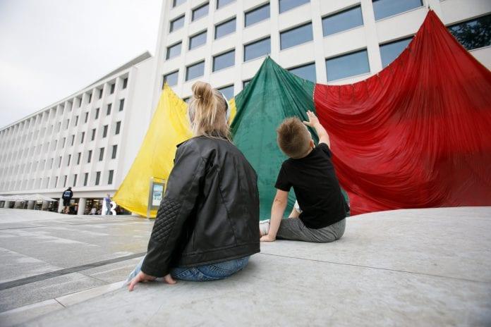 mama sėdi su vaiku prie Lietuvos vėliavos