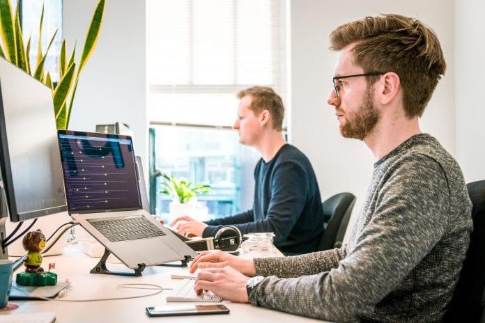 Darbuotojai sėdi prie kompiuterio