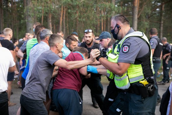 Žmonės nuo kelio prie Rūdninkų poligono nustumti jėga, neramumus malšino riaušių policija