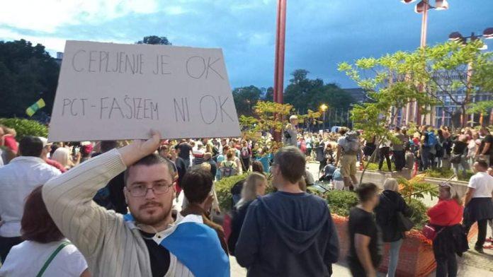 """Protestuotojas Liublianoje laiko plakatą """"Vakcinacija yra gerai, valdžios fašizmas - ne"""